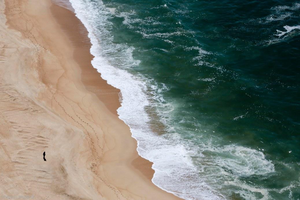 Menschenleerer Strand von Nazaré und Mann auf Atlantik blickend.