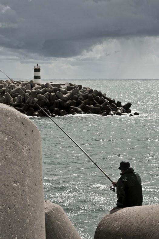 Angler in Nazaré vor Leuchtturm