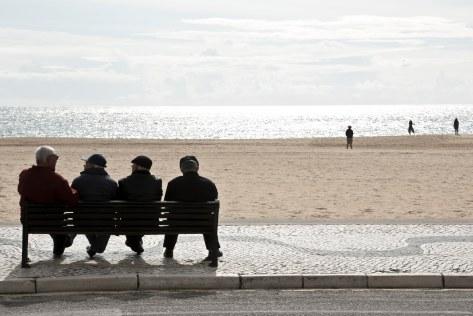vier alte Männer auf Strand-Bank in Nazaré