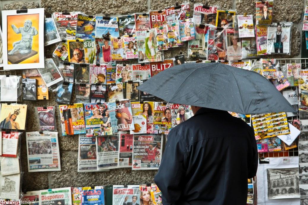 Mann mit Regenschirm vor Kiosk in Portugal