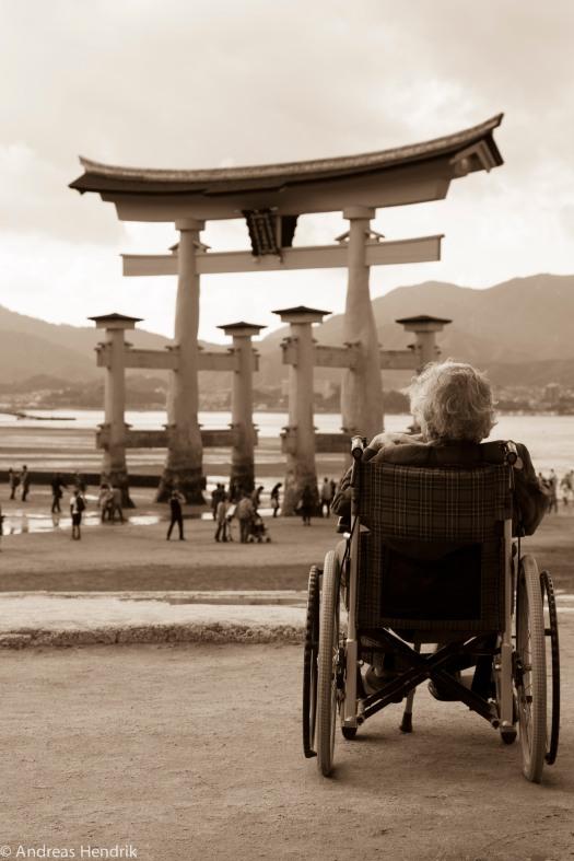 Old man and Torii Itsukushima-Schrein